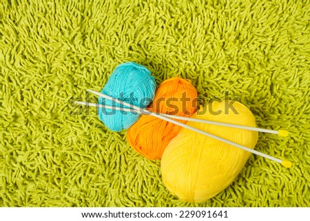 Knitting yarn balls and needles over green carpet background - stock photo