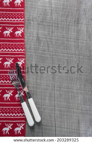 Knives and forks on wooden christmas background in red for a menu card. - stock photo
