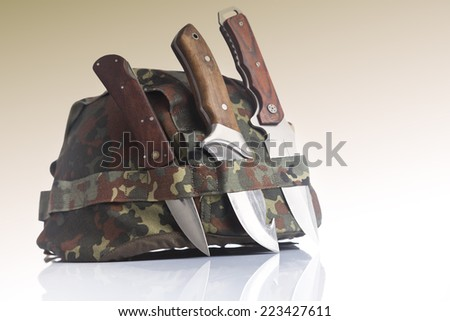 Knives and military helmet - stock photo