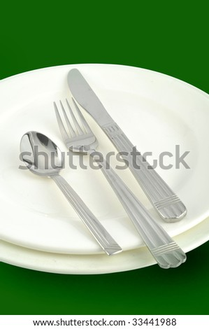 Knives, forks, spoons, and plates in green background