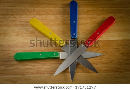 knives on wood, red, yellow, blue, green  - stock photo