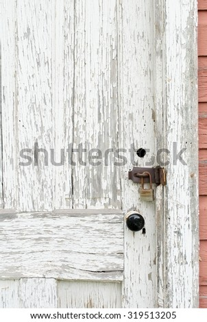 Knob and Lock on a Weatherbeaten Door of an Old House - stock photo