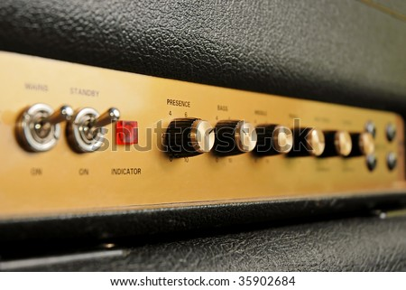 Knobs on a guitar amp (shallow DOF) - stock photo