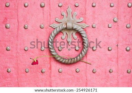 Knocker on a red medieval wooden door with a rose placed in it - stock photo