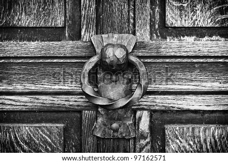knocker on the wooden door black and white