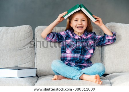 Knowledge assimilate better this way! Cheerful little girl holding book over her head and looking at camera with smile while sitting on the couch in lotus position at home - stock photo