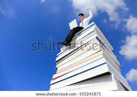 Knowledge is power - Happy business man using pc computer and sitting on a stack Of Books - stock photo