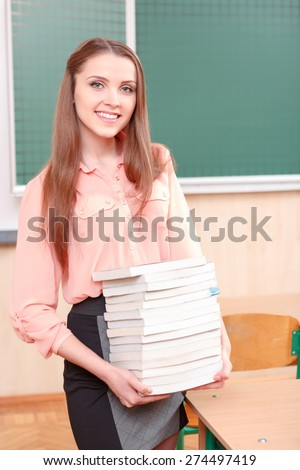 Knowledge is power. Young beautiful girl standing and holding pile of books on background of classroom - stock photo