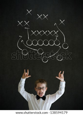 Knowledge rocks boy dressed up as business man with chalk American football strategy on blackboard background - stock photo