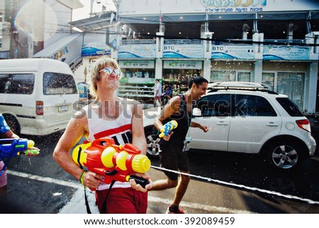 KO SAMUI, THAILAND - APRIL 13: Unidentified man shooting water at other people in  Songkran Festival (Thai New Year) on April 13, 2014 in Chaweng Main Road, Ko Samui island, Thailand.