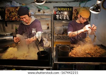 KOBE, JAPAN - DEC 14: Sobameshi, pan-fried ramen-style noodles with fried rice, being cooked by two at one of tens yatai, mobile food stalls, located by Kobe Luminarie on Dec 14, 2013 in Kobe, Japan. - stock photo