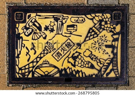 KOBE, JAPAN - OCTOBER 26: Manhole Cover in Kobe, Japan on October 26, 2014. Signs and symbols of important places that represent Kobe put down onto a manhole along a street in Kobe city