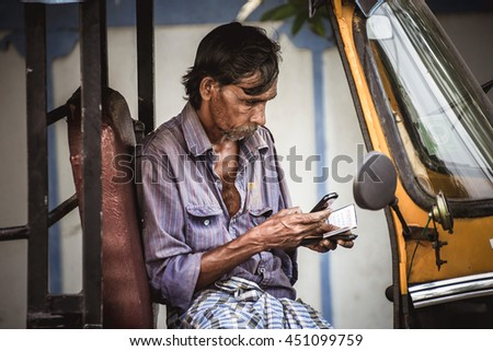 KOCHI/INDIA - NOVEMBER 22, 2015: Unidentified indian tuk-tuk driver looks at his mobile phone in  Kochi, India
