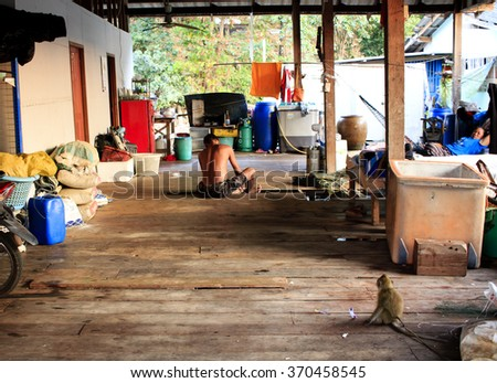 KOH KOOD, THAILAND - JANUARY 6, 2016 : Man, visible from behind, sitting in the middle of the room in the poor fisherman's village.  - stock photo