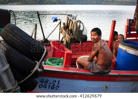 KOH KOOD, THAILAND - JANUARY 6th, 2016 : Thai man smiling at camera from the fishing boat in the poor fisherman's village.  - stock photo