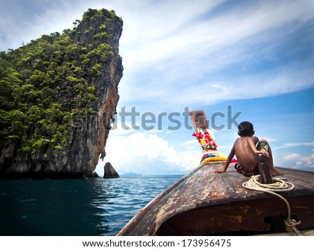 Koh Phi Phi, Thailand - May 09: Boy on traditional Thai long tail boat on the way to famous Maya Bay, Ko Phi Phi Island, Thailand. - stock photo