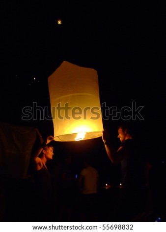KOH TAO, THAILAND - DECEMBER 23: People light Chinese sky lanterns on the beach to celebrate Christmas on December 23, 2007 in Koh Tao. - stock photo
