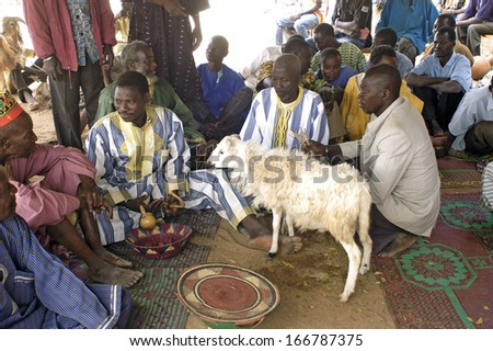 KOKEMNOURE, BURKINA FASO - FEBRUARY 24: Establishment of the new chief of village of Kokemnoure. A guest brings a gift to offer it to the new chief of village Andre Silga, february 24, 2007 - stock photo