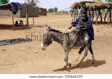 KOKEMNOURE, BURKINA FASO - FEBRUARY 21: Two children walking in the village of Kokemnoure donkey in a good mood, february 21, 2007. - stock photo