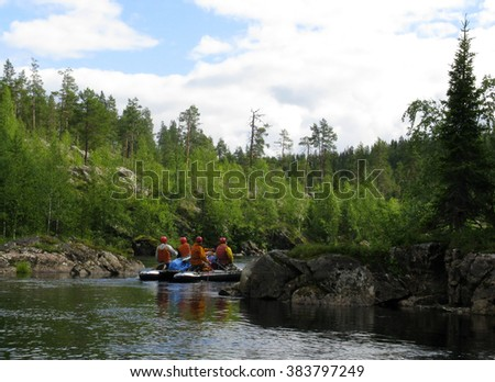 KOLA PENINSULA, RUSSIA - AUGUST 11 - Man on an inflatable catamaran at rough river in Kola Peninsula on August 11, 2008.