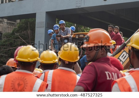 KOLKATA -APRIL 1:A rescue worker taking picture of a dead body (not visible) during the rescue effort after an under construction flyover collapsed killing 27 people on April 1, 2016 in Kolkata,India.