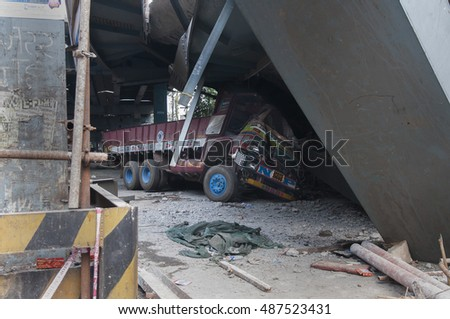 KOLKATA - APRIL 1: A truck stuck underneath during the rescue effort after an under construction flyover collapsed killing 27 people on April 1, 2016 in Kolkata, India.