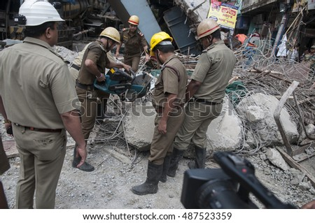 KOLKATA - APRIL 1: Police officers cutting concrete with gas cutter during the rescue effort after an under construction flyover collapsed killing 27 people on April 1, 2016 in Kolkata, India.