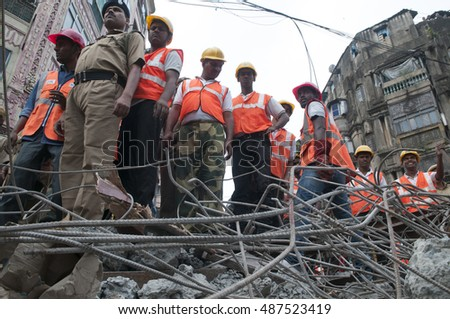 KOLKATA - APRIL 1: Rescue workers standing on concrete debris during the rescue effort after an under construction flyover collapsed killing 27 people on April 1, 2016 in Kolkata, India.