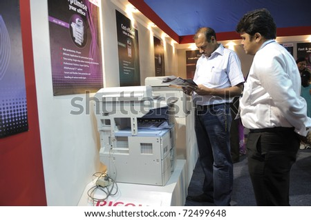 KOLKATA- FEBRUARY 20: A customer reading the brochure of a photocopier, during the Information and Communication Technology (ICT) conference and exhibition in Kolkata, India on February 20, 2011. - stock photo