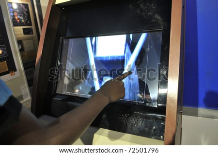 KOLKATA- FEBRUARY 20: A  human finger plays around with a touch screen, during the Information and Communication Technology (ICT) conference and exhibition in Kolkata, India on February 20, 2011. - stock photo
