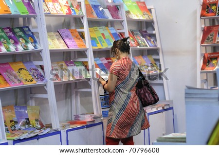 KOLKATA- FEBRUARY 4: A lonely woman flips through books  during the 2011 Kolkata Book fair  in Kolkata, India on February 4, 2011. - stock photo
