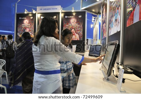 KOLKATA- FEBRUARY 20:  A sales associate explaining a customer during the Information and Communication Technology (ICT) conference and exhibition in Kolkata, India on February 20, 2011. - stock photo