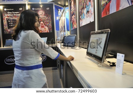 KOLKATA- FEBRUARY 20: A sales associate playing around with an HP DreamScreen ,during the Information and Communication Technology (ICT) conference and exhibition in Kolkata,India on February 20,2011. - stock photo