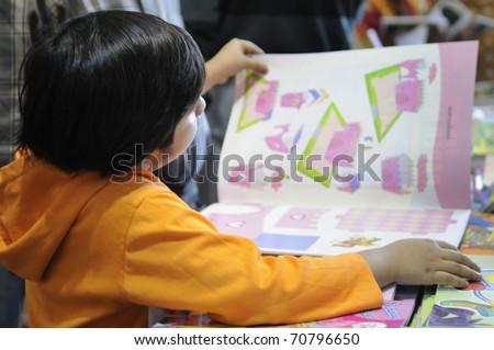 KOLKATA- FEBRUARY 4: A small kid flips through a drawing book before buying during the 2011 Kolkata Book Fair in Kolkata, India on February 4, 2011. - stock photo