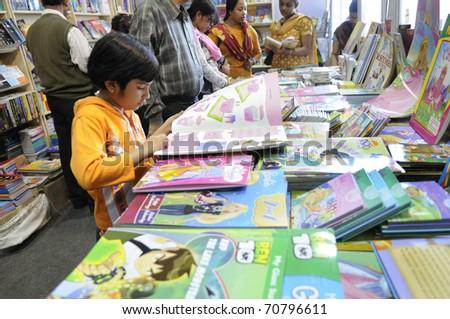 KOLKATA- FEBRUARY 4: A  small kid flips through her favorite books  during the 2011 Kolkata Book fair in Kolkata, India on February 4, 2011. - stock photo