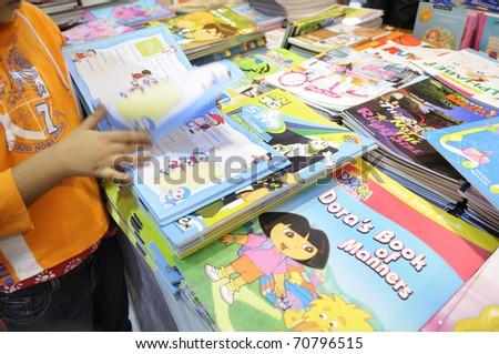 KOLKATA- FEBRUARY 4: A small kid flips through the pages of a cartoon book during the 2011 Kolkata book fair in Kolkata, India on February 4, 2011. - stock photo
