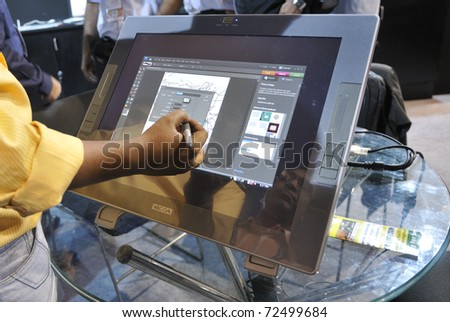 KOLKATA- FEBRUARY 20: A visitor  draws on a screen with a cordless touch pen during the Information and Communication Technology (ICT) conference and exhibition in Kolkata, India on February 20,2011. - stock photo