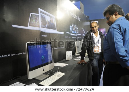 KOLKATA- FEBRUARY 20: A visitor looks towards a MAC computer during the Information and Communication Technology (ICT) conference and exhibition in Kolkata, India on February 20, 2011. - stock photo