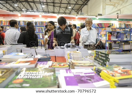 KOLKATA- FEBRUARY 4: A young guy flips though a book and an old man looking at it ,during the 2011 Kolkata Book fair in Kolkata, India on February 4, 2011. - stock photo