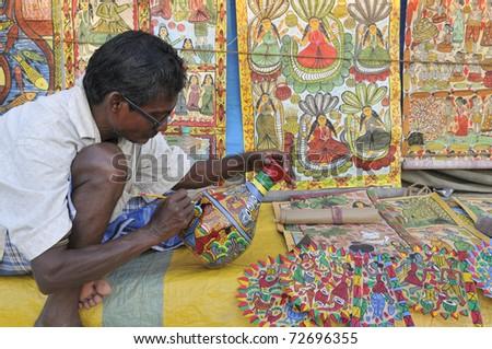 KOLKATA- FEBRUARY 23:  An old man painting a pottery ,during the Handicraft Fair on February 23, 2011 in Kolkata, India. - stock photo