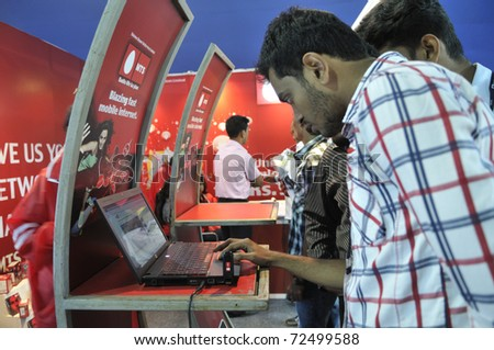 KOLKATA- FEBRUARY 20:Curious customers checking the speed of an internet stick during the Information and Communication Technology (ICT) conference and exhibition in Kolkata,India on February 20,2011. - stock photo