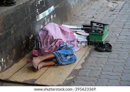 KOLKATA - FEBRUARY 09: Homeless people sleeping on the footpath of Kolkata. on February 09, 2014 in Kolkata, India - stock photo