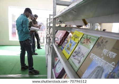 KOLKATA- FEBRUARY 4: Kolkata teens read books to consider during the 2011 Kolkata Book Fair  in Kolkata, India on February 4, 2011. - stock photo