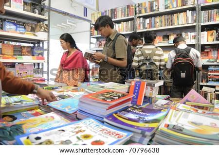 KOLKATA- FEBRUARY 4: People flip through books during the 2011 Kolkata Book Fair in Kolkata, India on February 4, 2011. - stock photo