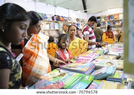 KOLKATA- FEBRUARY 4: People flip through books for kid at a kid book stall  during the 2011 Kolkata Book fair  in Kolkata, India on February 4, 2011. - stock photo