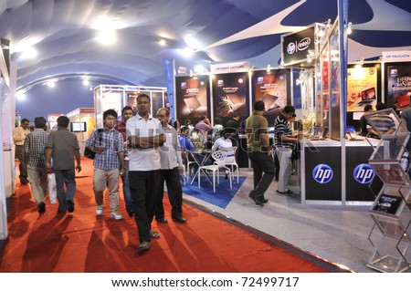 KOLKATA- FEBRUARY 20: People passing by a HP Pavilion during the Information and Communication Technology (ICT) conference and exhibition in Kolkata, India on February 20, 2011. - stock photo