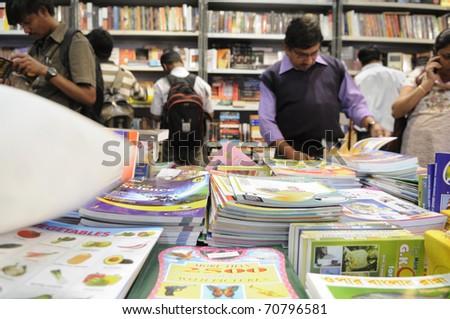 KOLKATA- FEBRUARY 4: People read books inside a book stall  during the 2011 Kolkata Book fair  in Kolkata, India on February 4, 2011. - stock photo