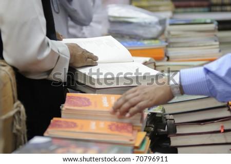 KOLKATA- FEBRUARY 4:People select and read books during the 2011 Kolkata Book Fair in Kolkata, India on February 4, 2011. - stock photo