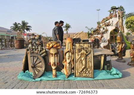 KOLKATA- FEBRUARY 23: Visitors deciding on sculptors and murals during the Handicraft Fair  on February 23, 2011 in Kolkata, India. - stock photo