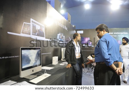 KOLKATA- FEBRUARY 20:  Visitors looking at a movie on a MAC computer, during the Information and Communication Technology (ICT) conference and exhibition in Kolkata, India on February 20, 2011. - stock photo